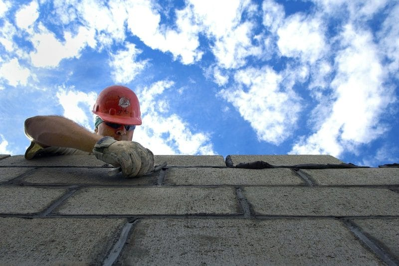 Maçon en train de monter un mur